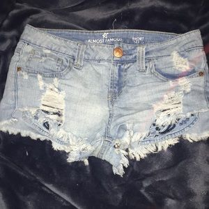 Ripped jean shorts with blue embroidered pockets